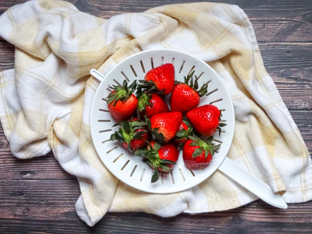 strawberries on a strainer and kitchen towel