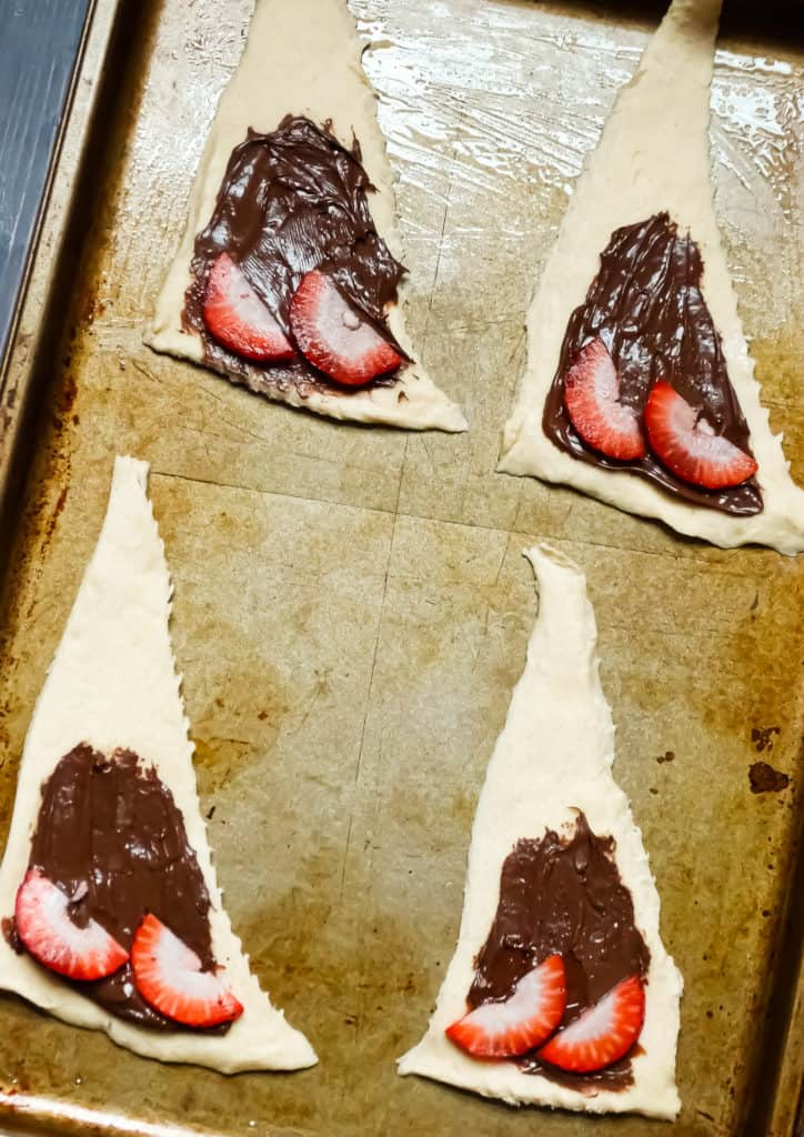 crescent rolls layered with nutella and sliced strawberries