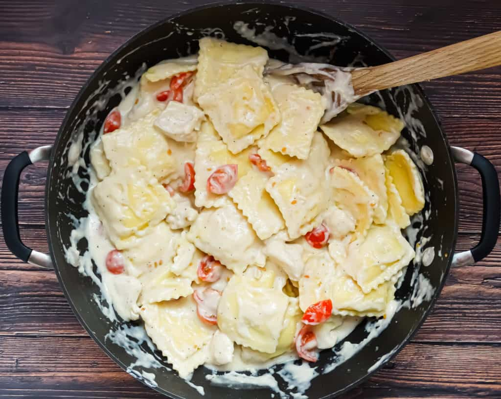 creamy one pot pasta with tomatoes and chicken in a wok