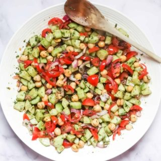 cucumber tomato salad with dressing in a white serving bowl