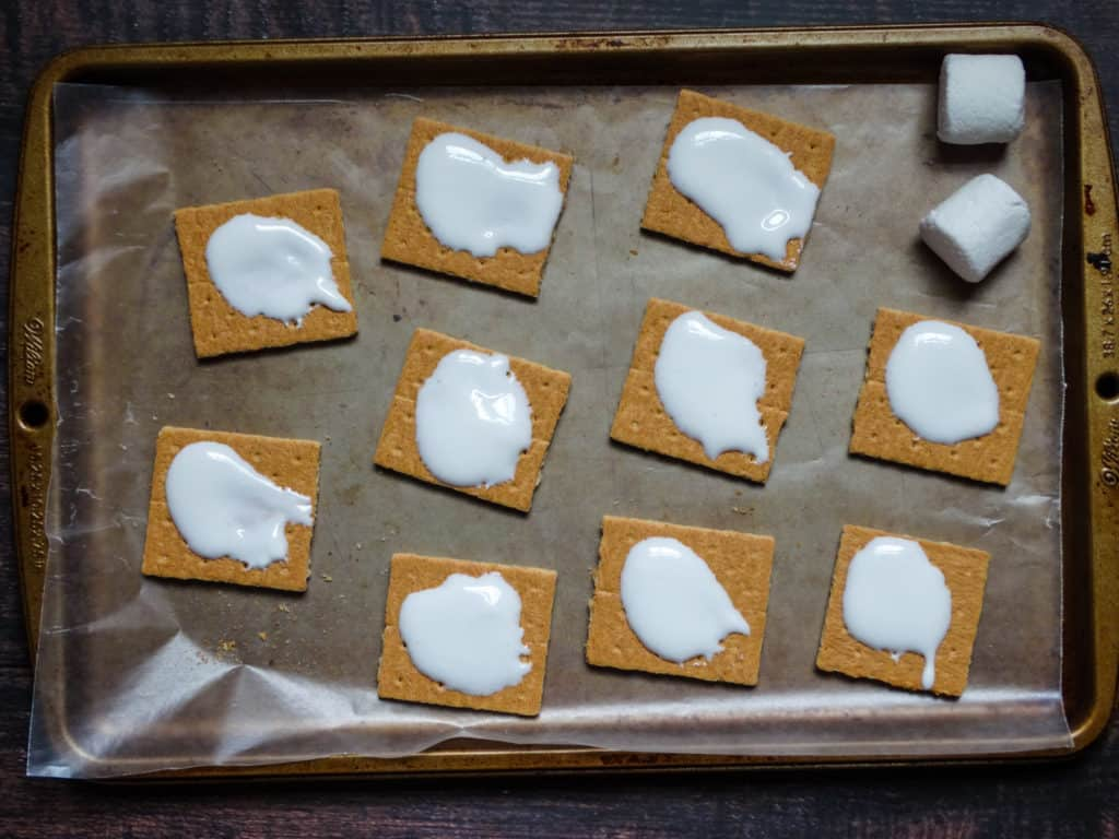 graham crackers topped with melted marshmallow on a baking sheet