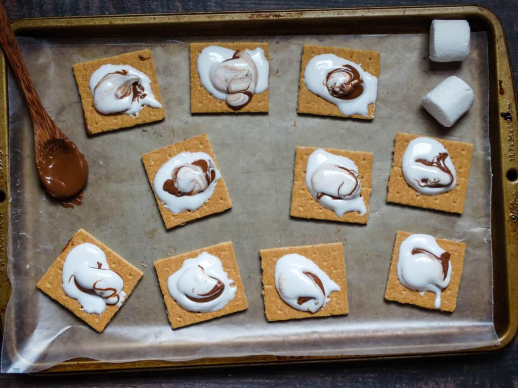 graham crackers topped with melted marshmallow and chocolate on a baking sheet