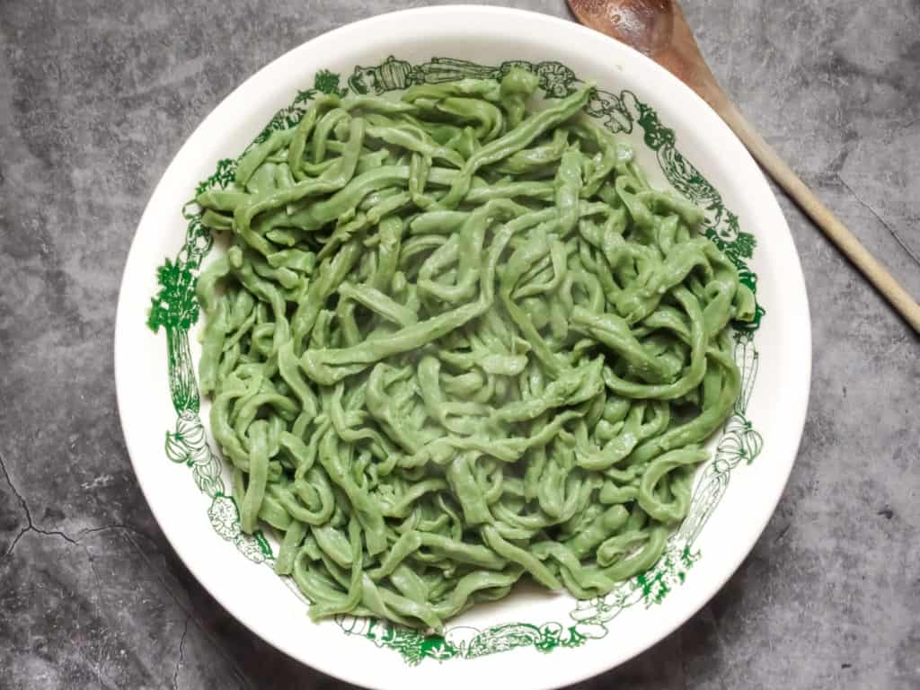 homemade spinach pasta dough for the bread machine in a white bowl