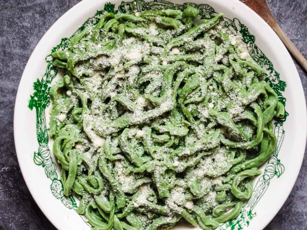 spinach pasta topped with parmesan cheese in a white bowl