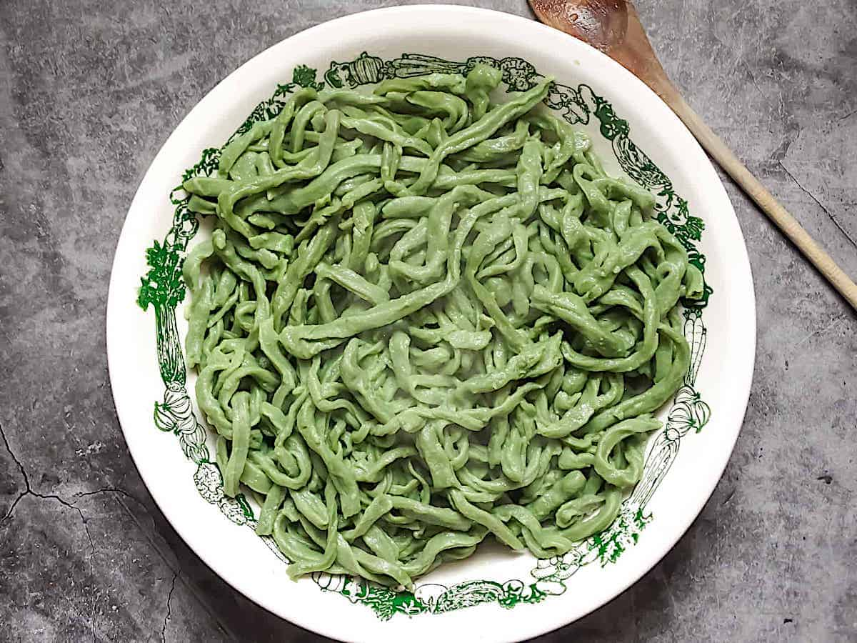 fresh cooked spinach pasta dough in a white bowl