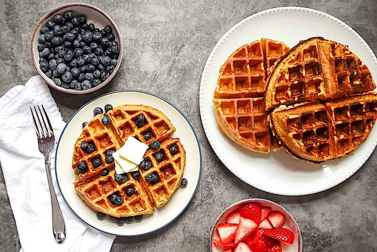 cottage cheese waffles on 2 plates served with a side of strawberries and blueberres
