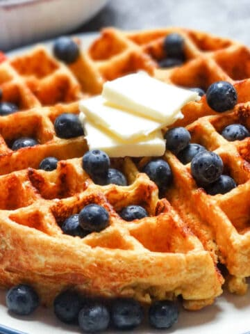 cottage cheese waffles on a plate with fruit and butter