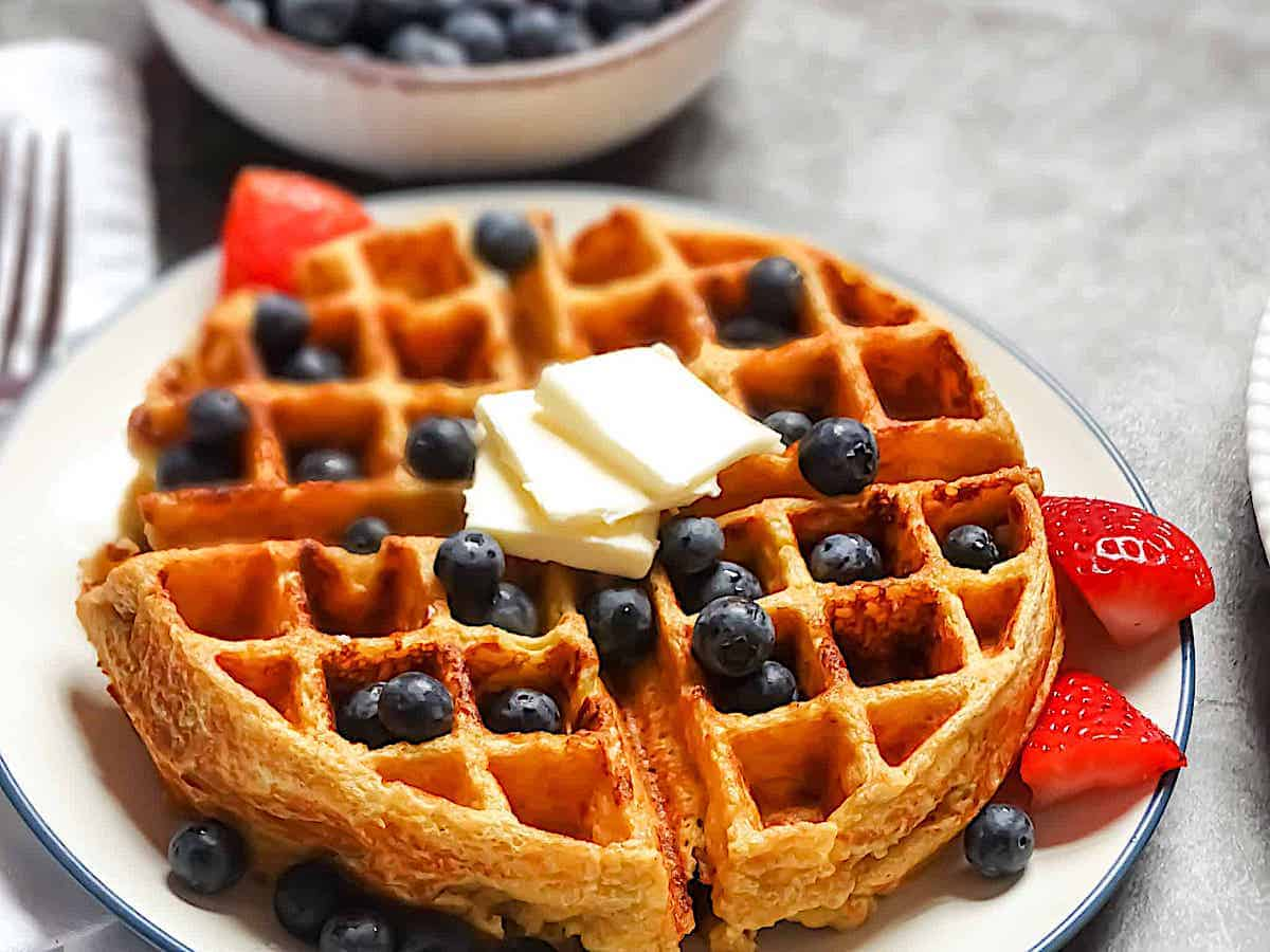 cottage cheese waffles on a plate topped with fruit and butter