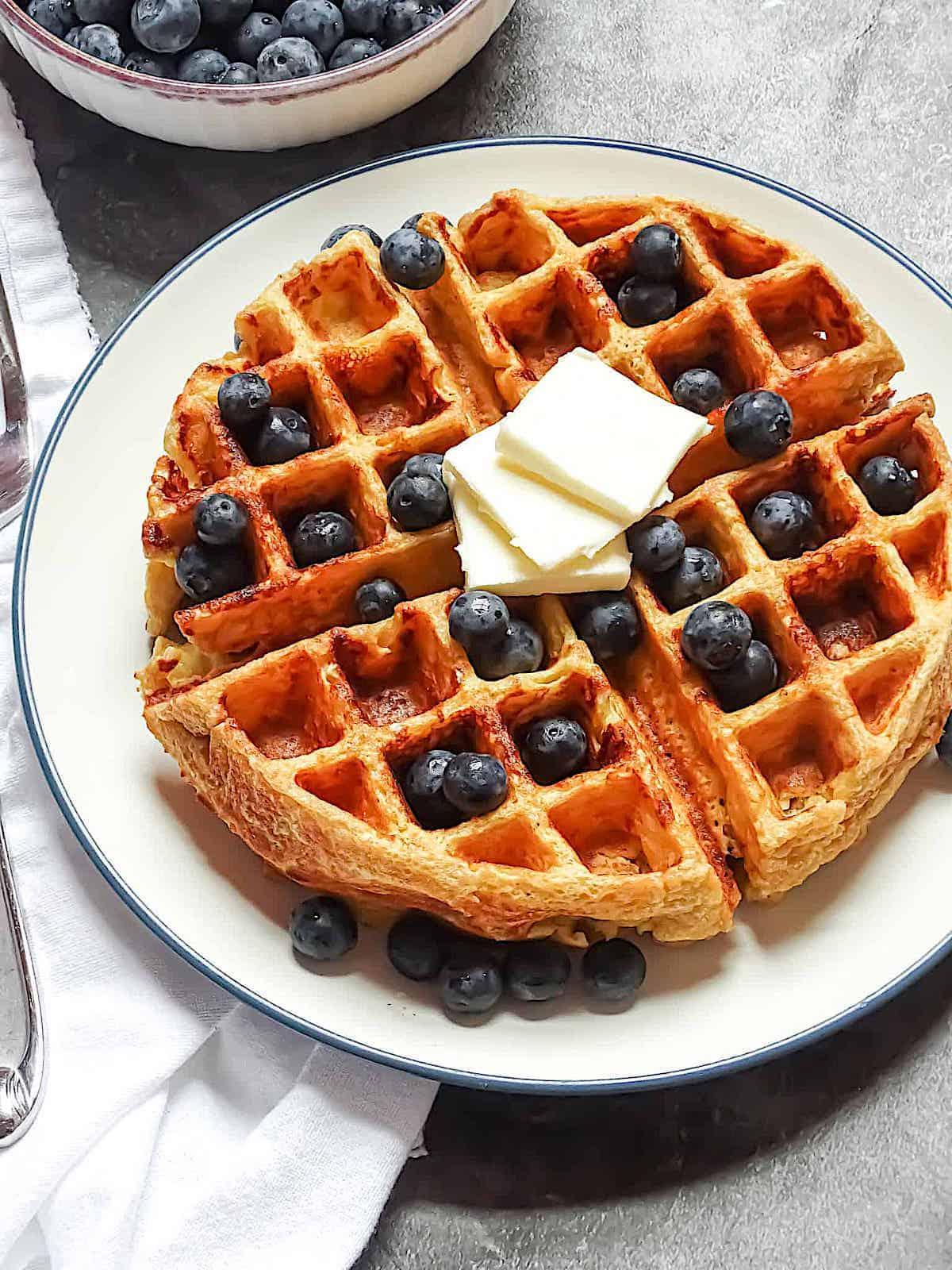 belgian waffles served with blueberries and butter