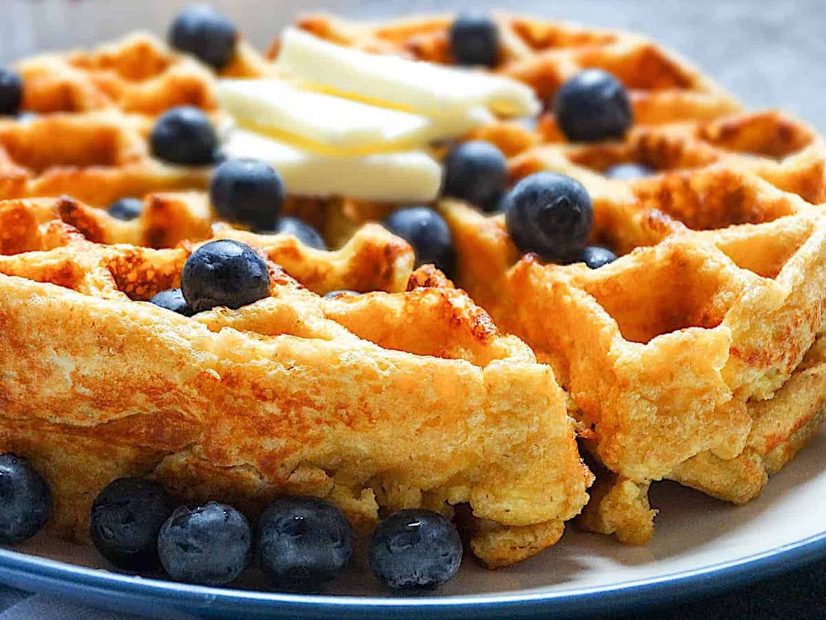 side shot of a cottage cheese waffle topped with blueberries and butter