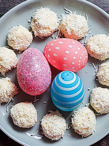 no bake cheesecake bites covered in shredded coconut on a plate with easter eggs