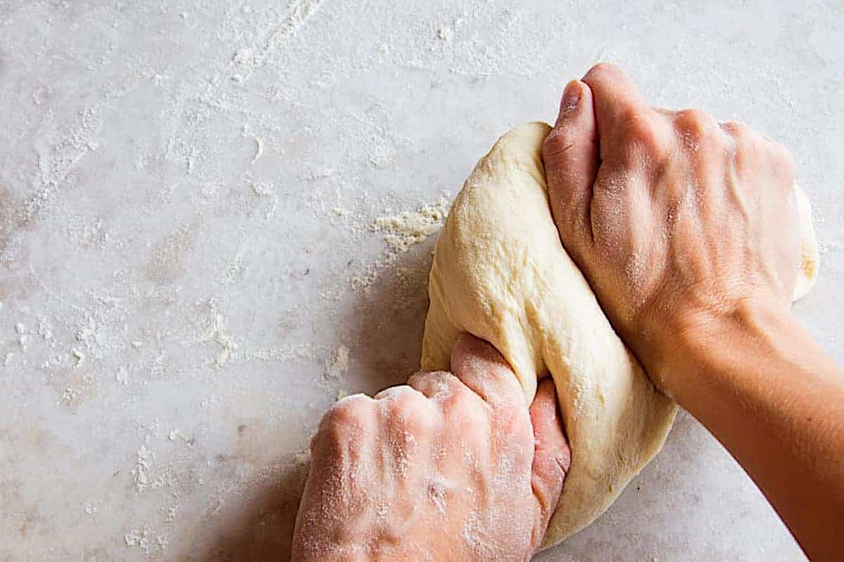thin crust pizza dough being kneaded by hand