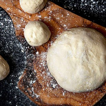 4 pizza dough balls on a cutting board