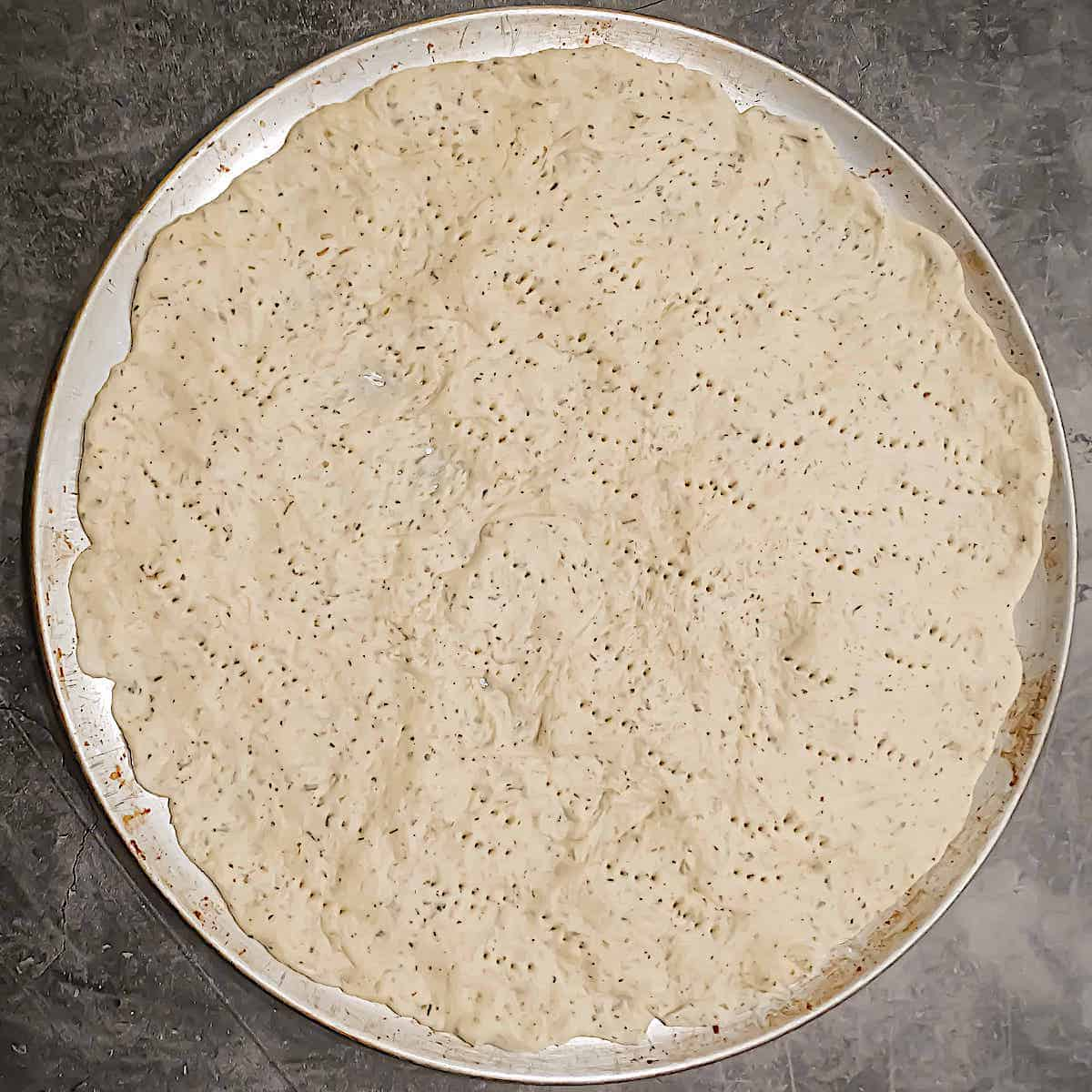 thin crust pizza dough spread into a circle on a pan with holes poked through the dough