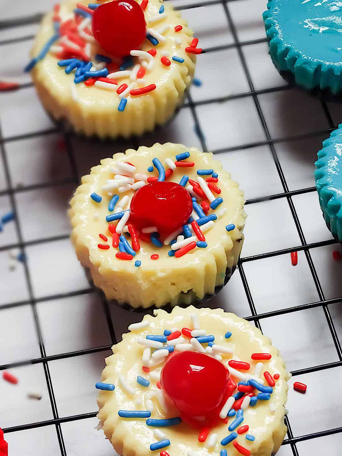 white mini  4th of july cheesecakes topped with cherries and sprinkles