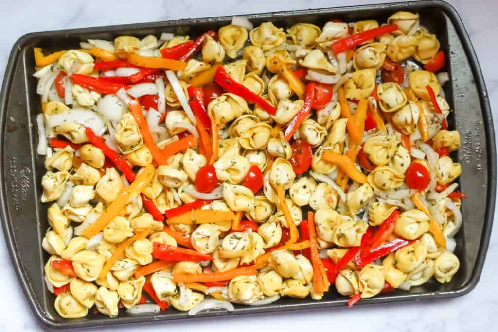 sheet pan tortellini with roasted vegetables on a baking pan