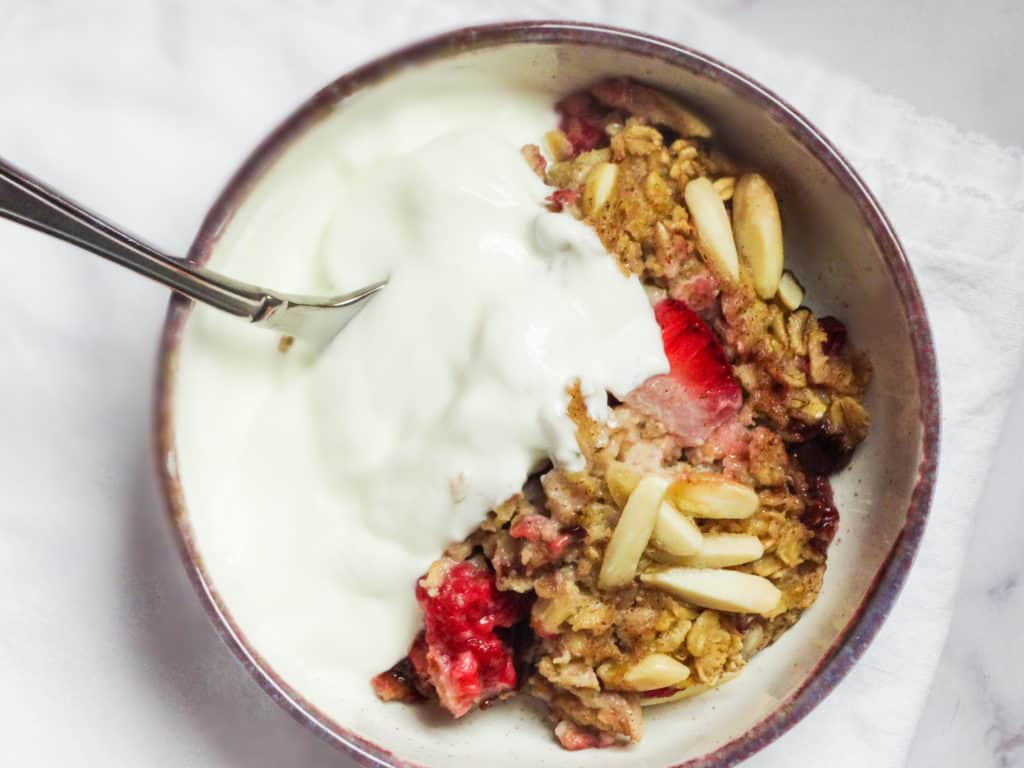 baked oatmeal with strawberries and raspberries in a bowl topped with yogurt