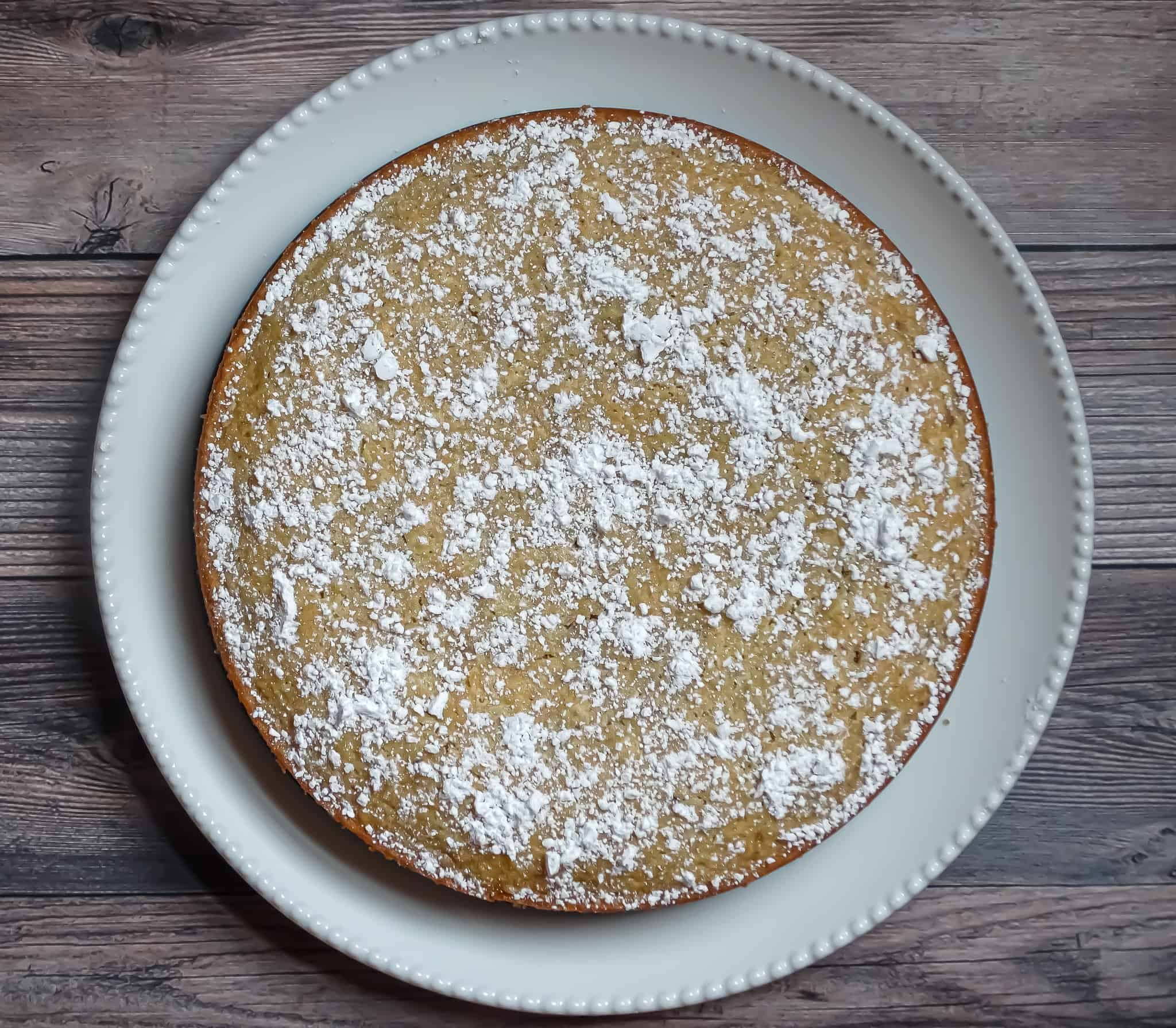 olive oil cake recipe sprinkled with powdered sugar on a white plate