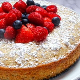 lemon olive cake topped with mixed berries and sprinkled with powdered sugar