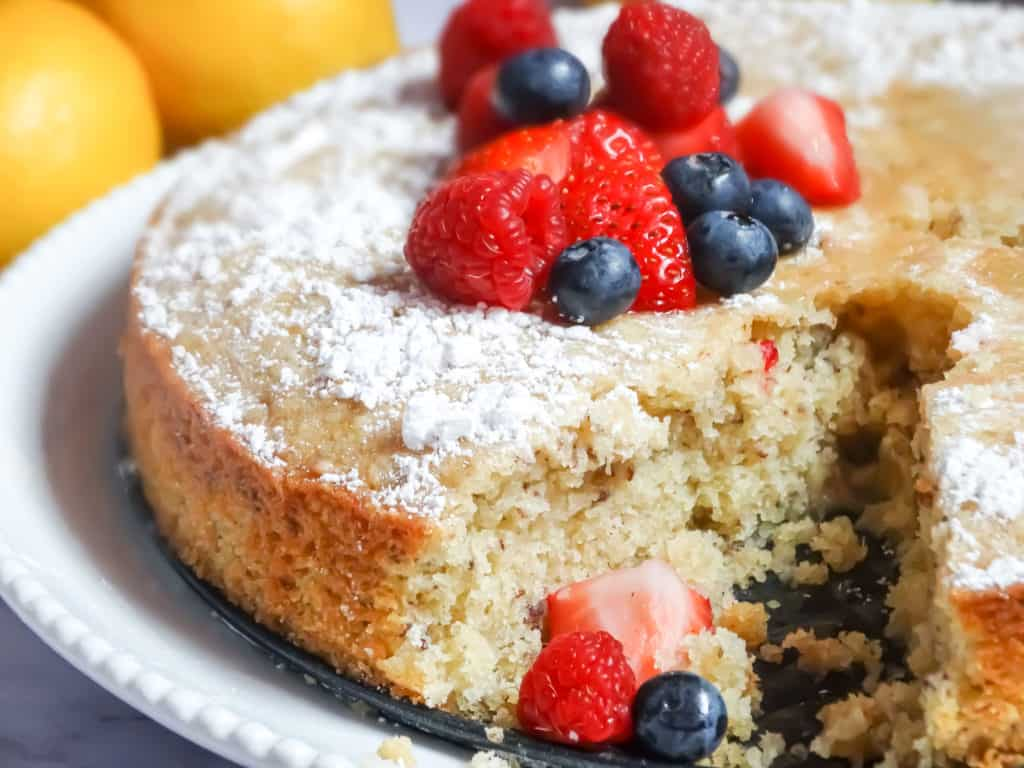 sliced olive oil cake topped with powdered sugar and berries