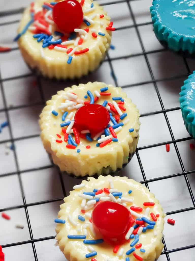 mini cheesecakes topped with cherry and sprinkles