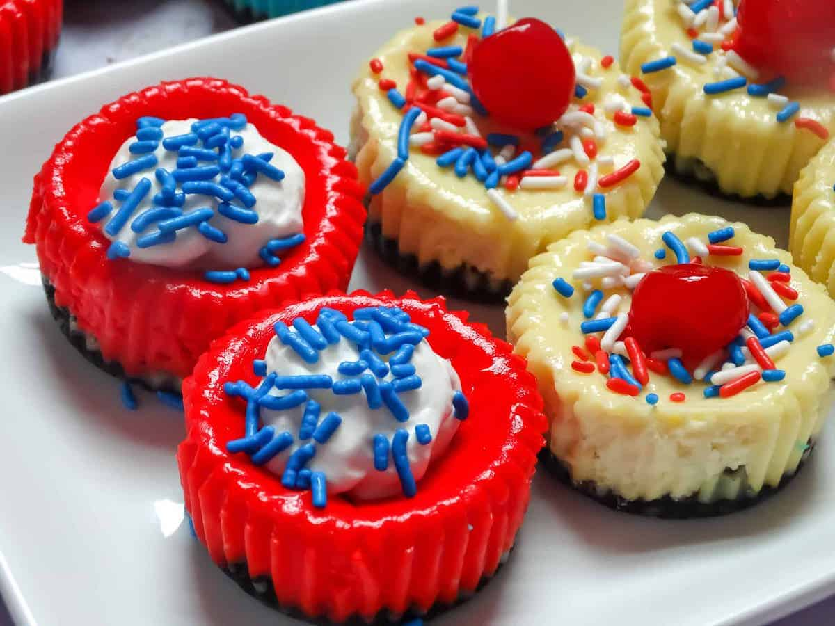 red mini cheesecake with blue sprinkles and whipped cream
