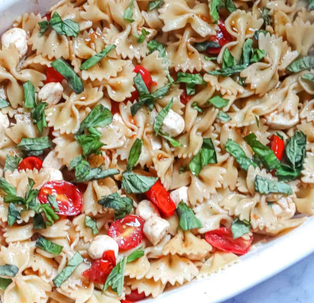 caprese pasta salad recipe in a white serving dish as a bbq side dish