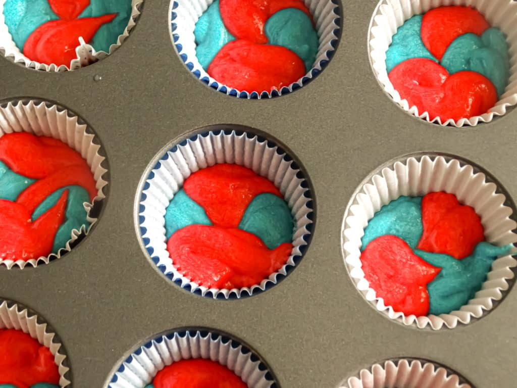 red and blue cupcake batter dolloped in cupcake liners