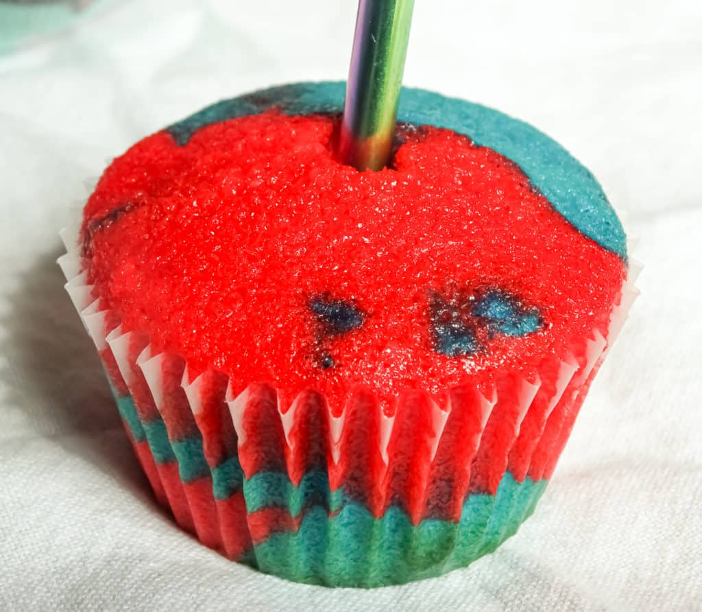patriotic cupcake with a straw in the center to create a hole for sprinkles