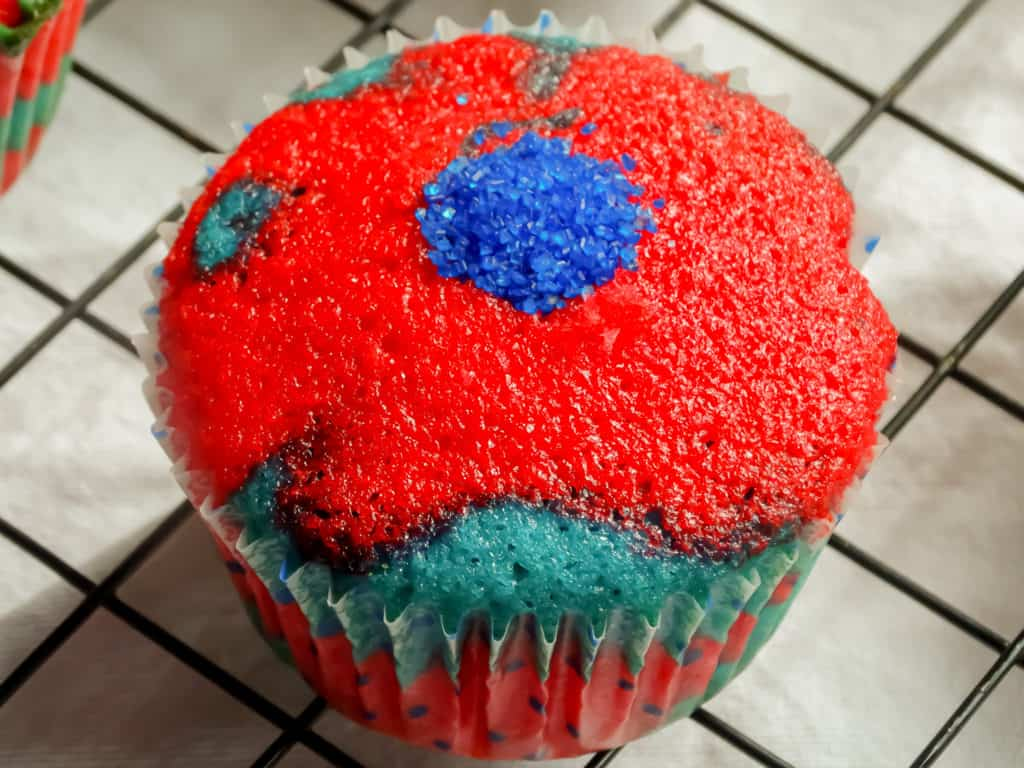 red white and blue cupcake filled with blue crystal sprinkles on a drying rack