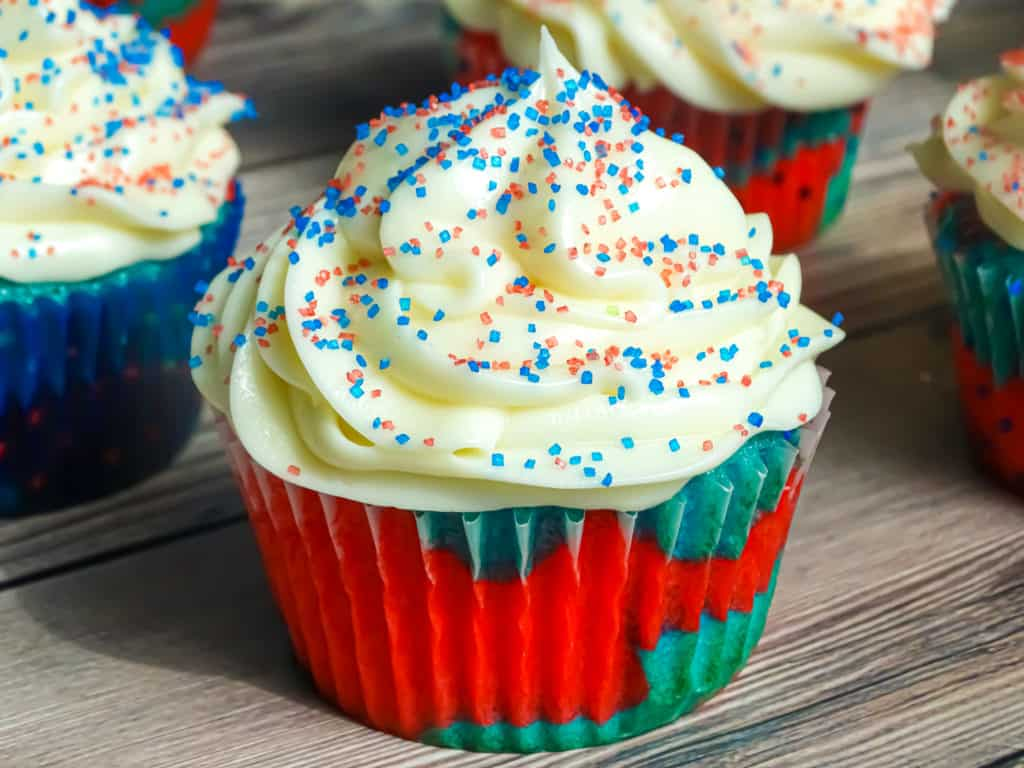 4th of July dessert: firecracker explosion cupcake with cream cheese frosting and red white and blue sprinkles, a tasty 4th of July dessert