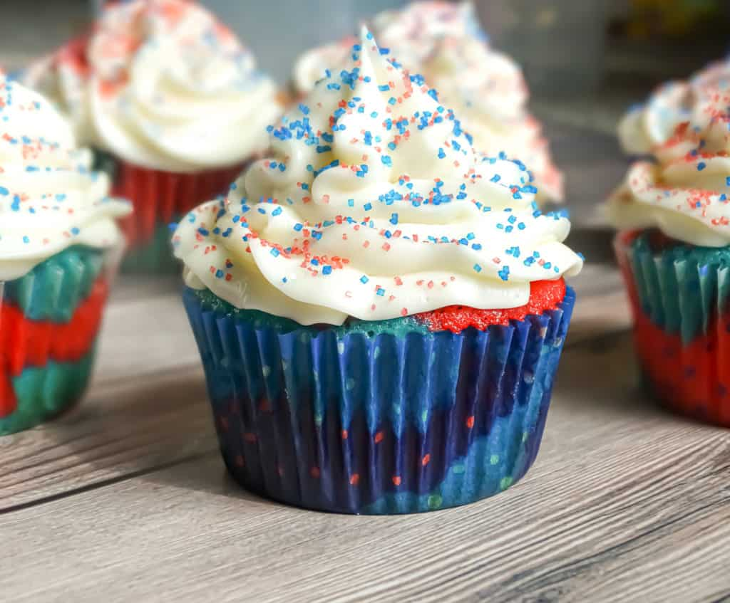 red and blue cupcakes with cream cheese frosting and sprinkles inside