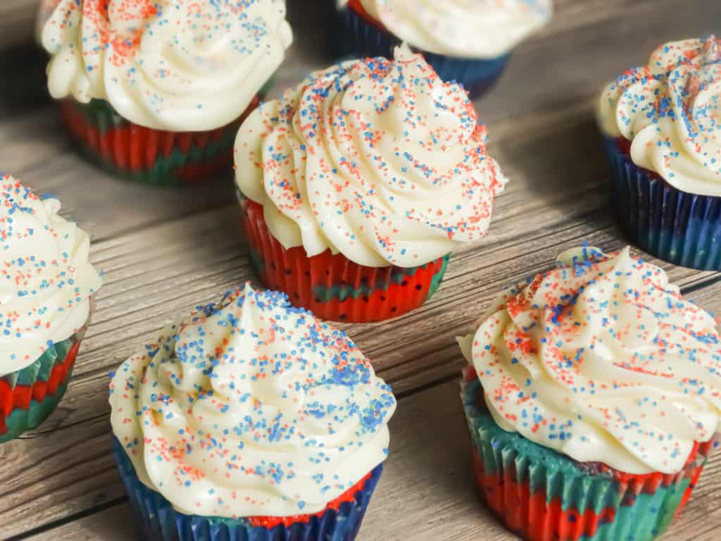 4th of July dessert: red white and blue cupcakes with sprinkles inside and cream cheese frosting