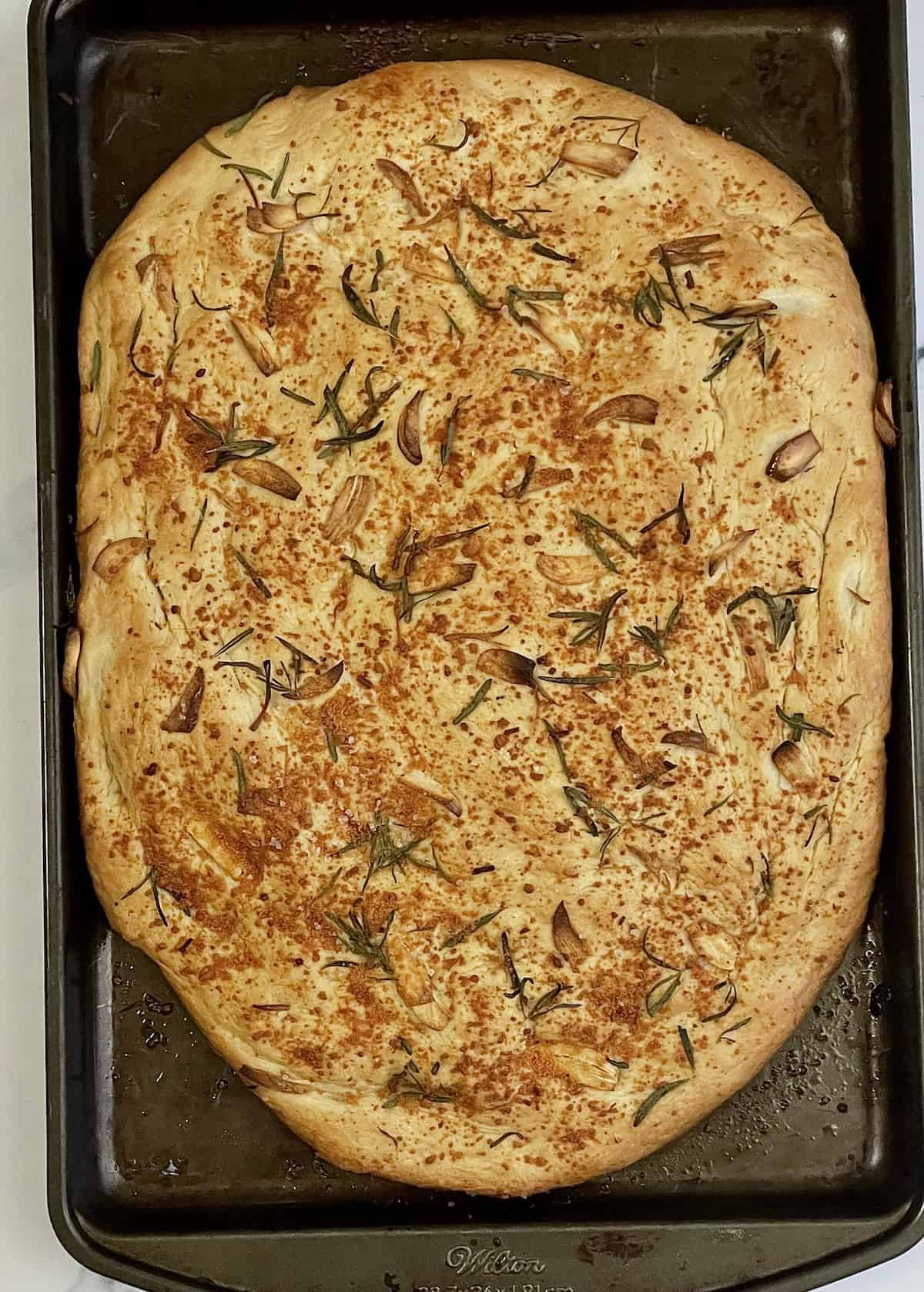 focaccia bread on a baking sheet topped with rosemary, garlic, and olive oil