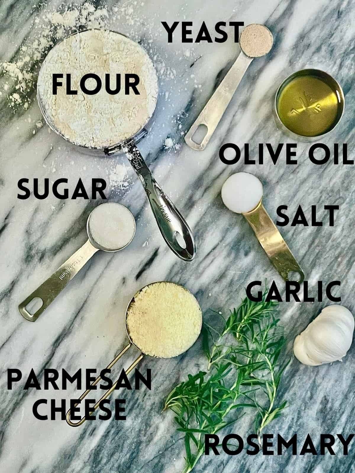 flour, sugar, oil, salt, yeast, rosemary, garlic, and cheese laid out on a cutting board