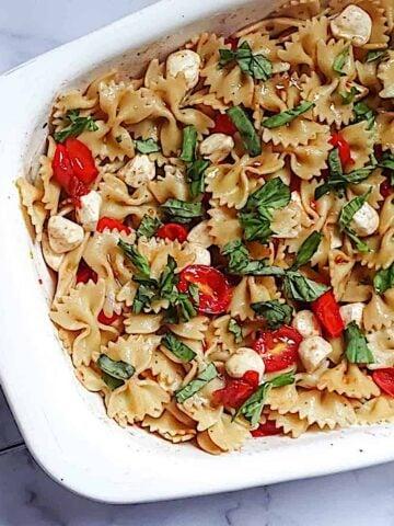 caprese pasta salad in a white serving dish