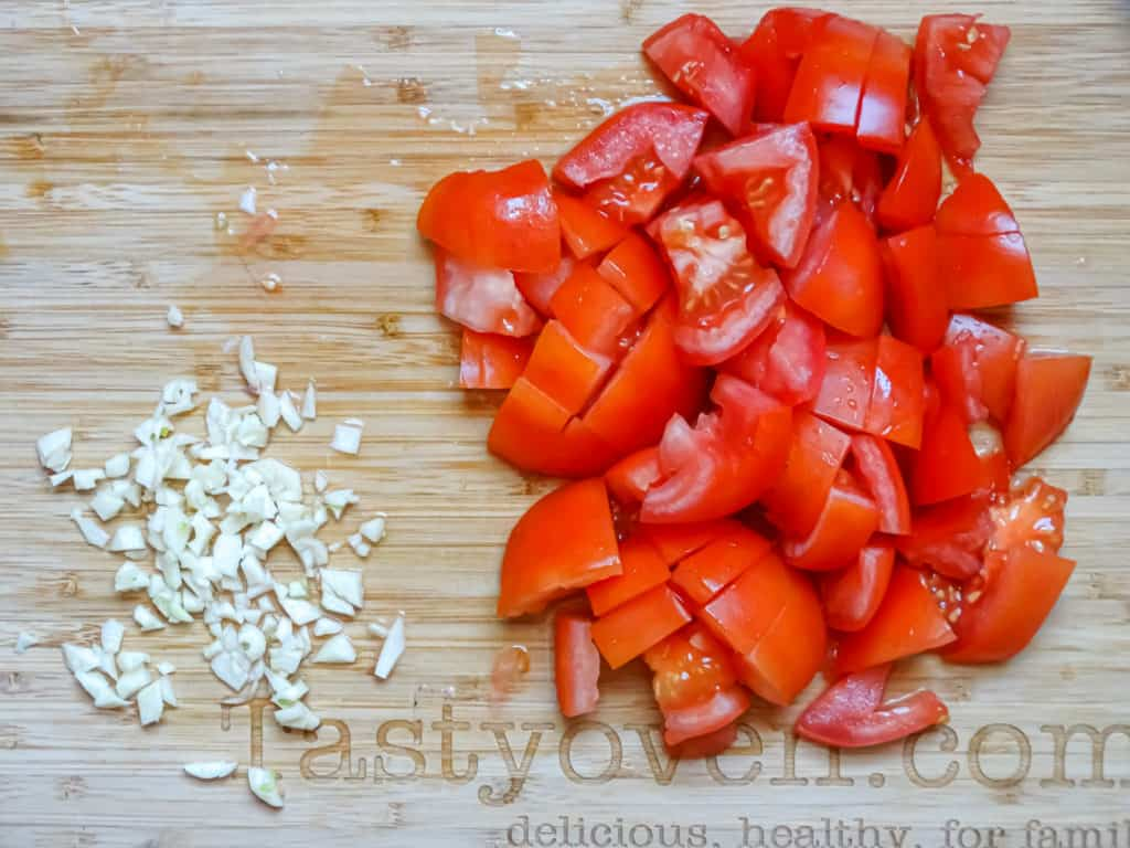 garlic and tomatoes chopped on a cutting board