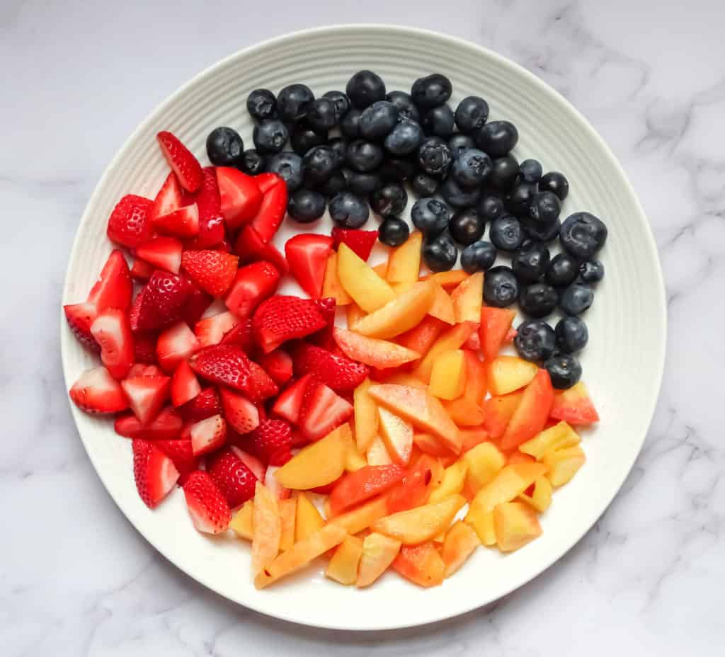 summer fruit salad ingredients on a white plate: blueberries, strawberries, and peaches
