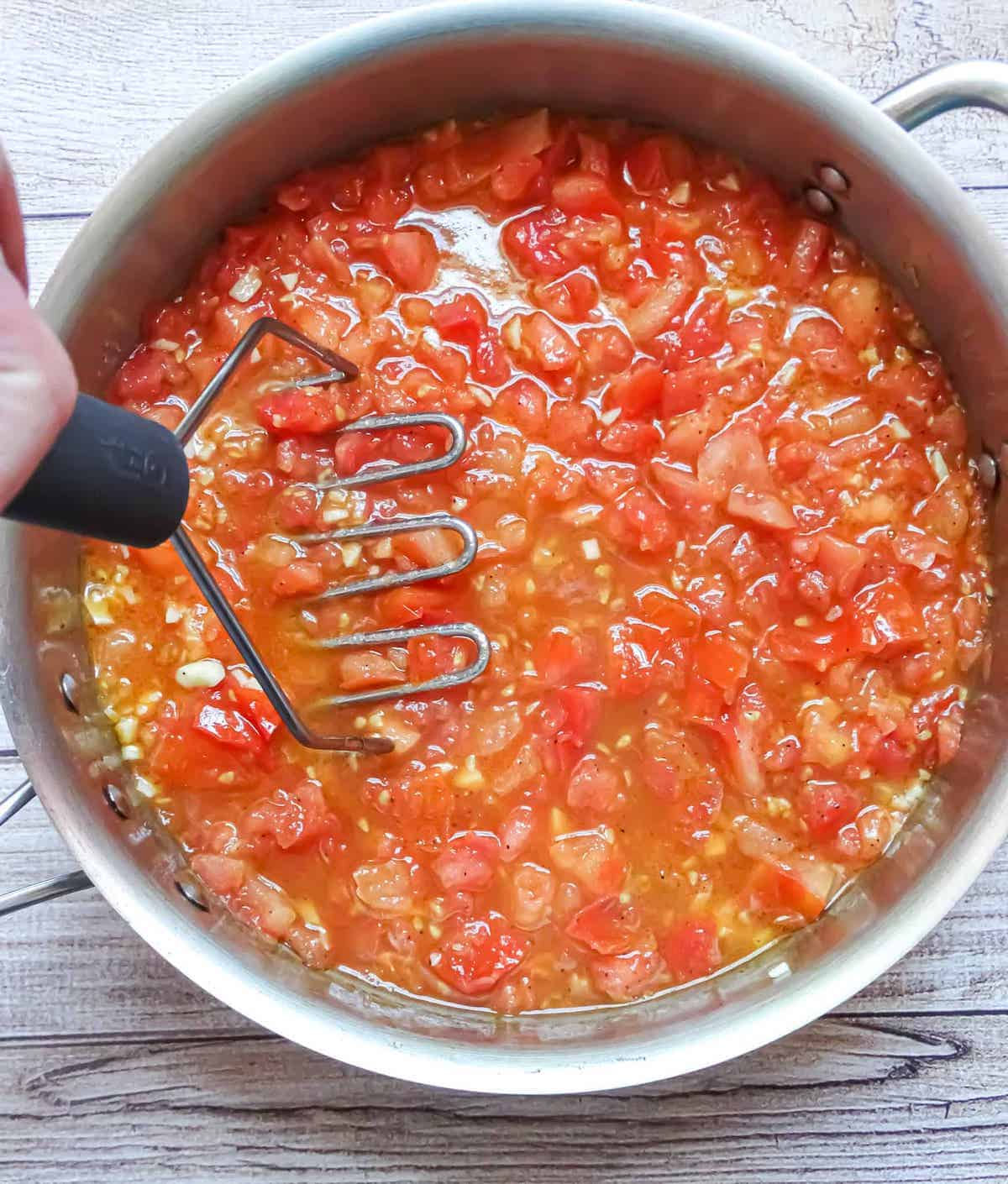 tomatoes and garlic crushed in a pan