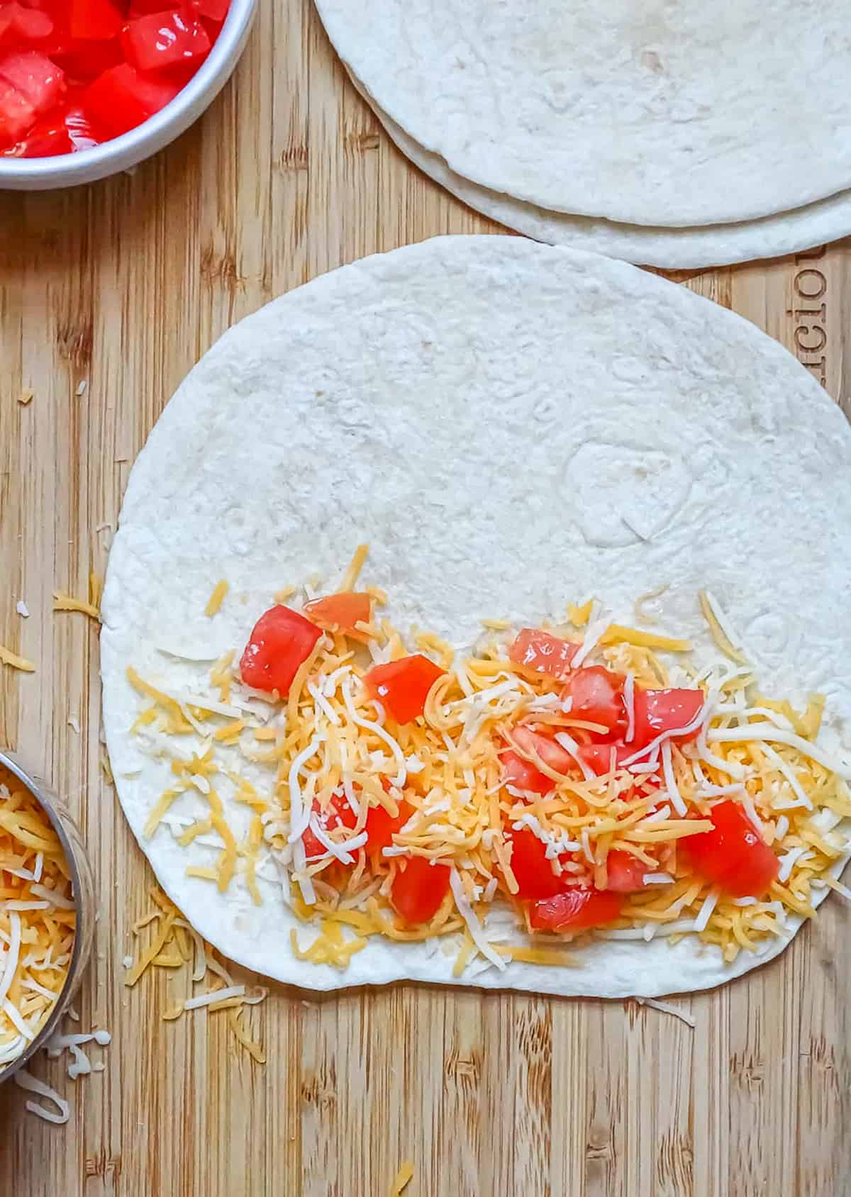 tortilla shell with cheese and tomatoes on 1 side