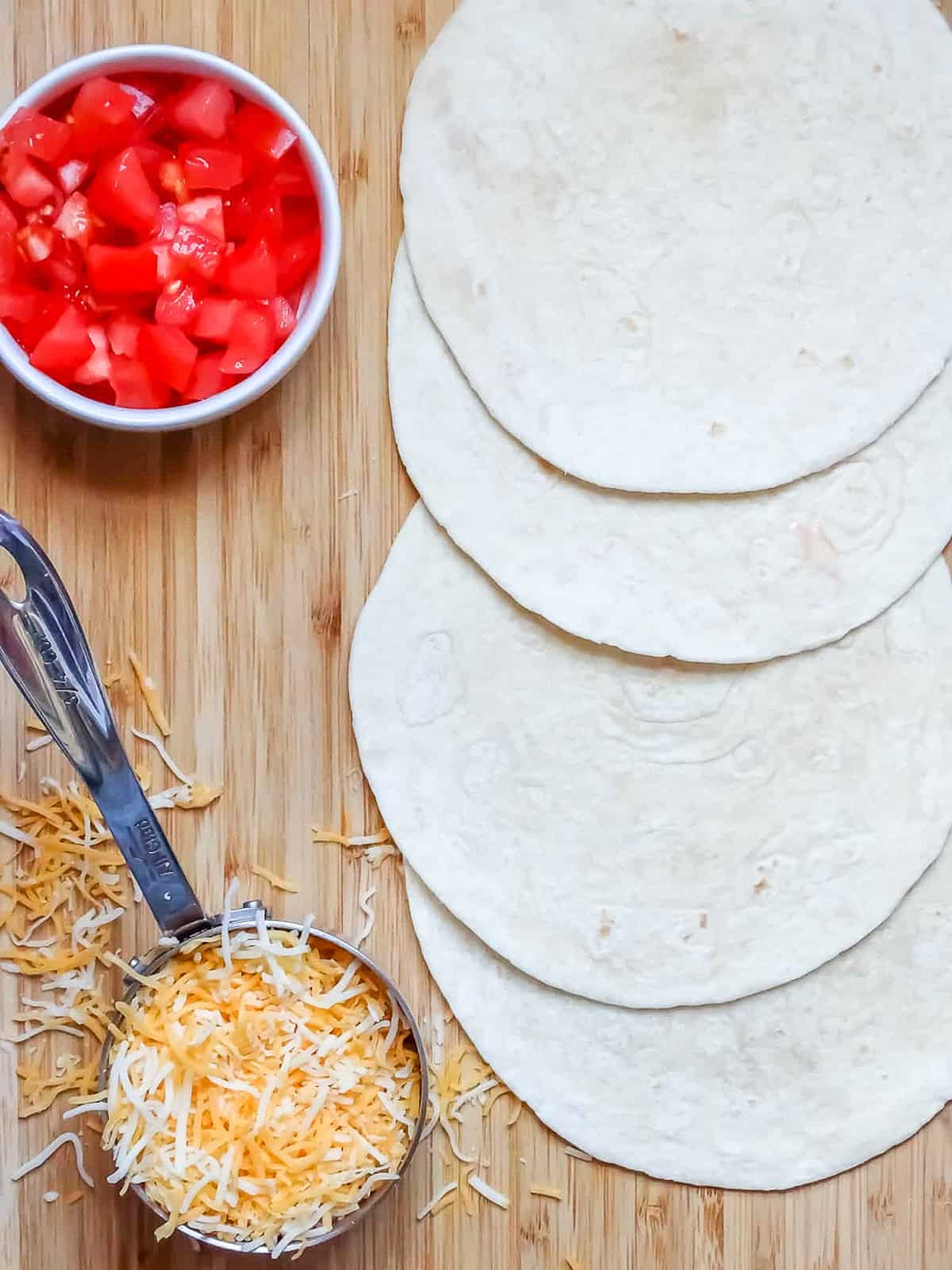 cheese, tomatoes, and tortillas on a cutting board