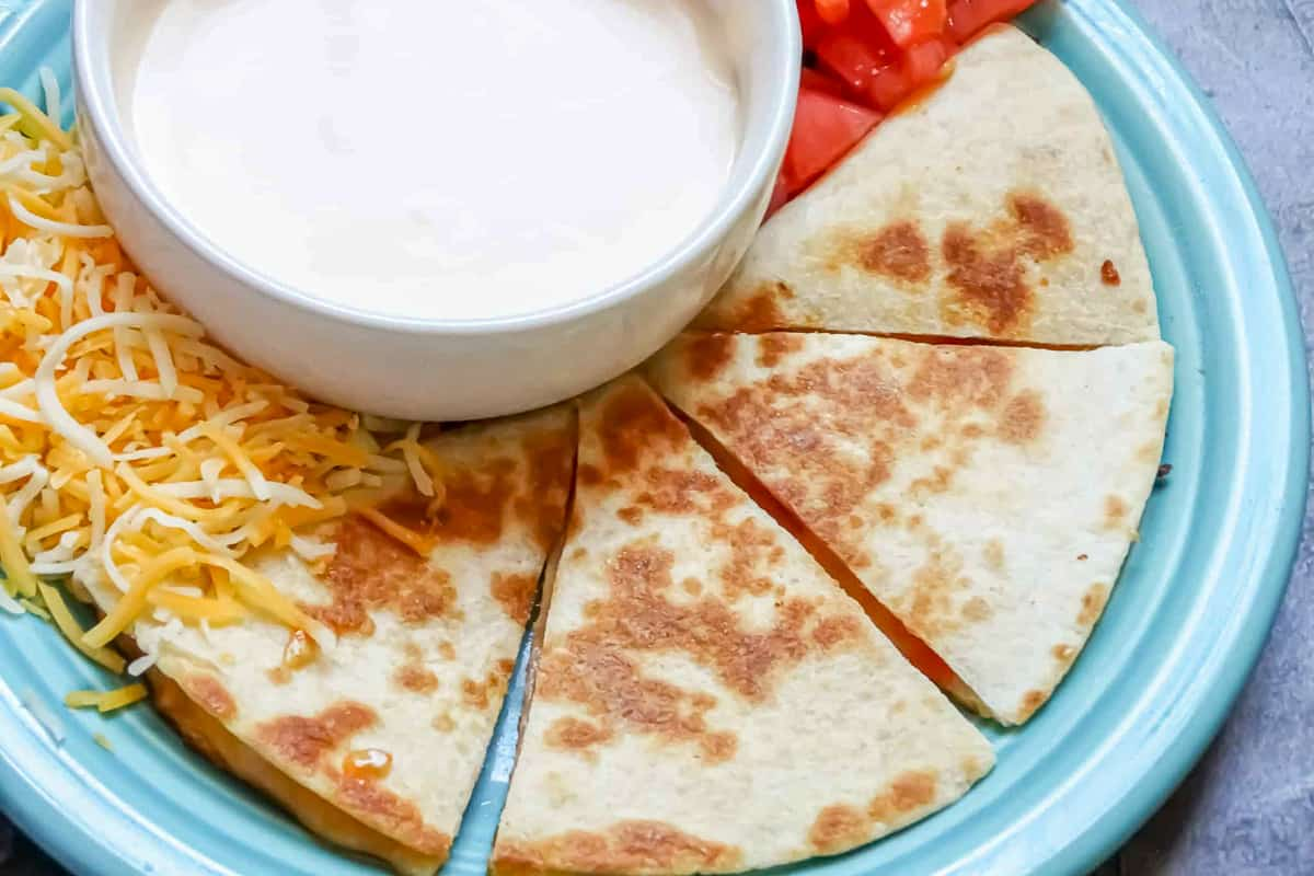 kids quesadillas sliced on a blue plate and served with sour cream and tomatoes