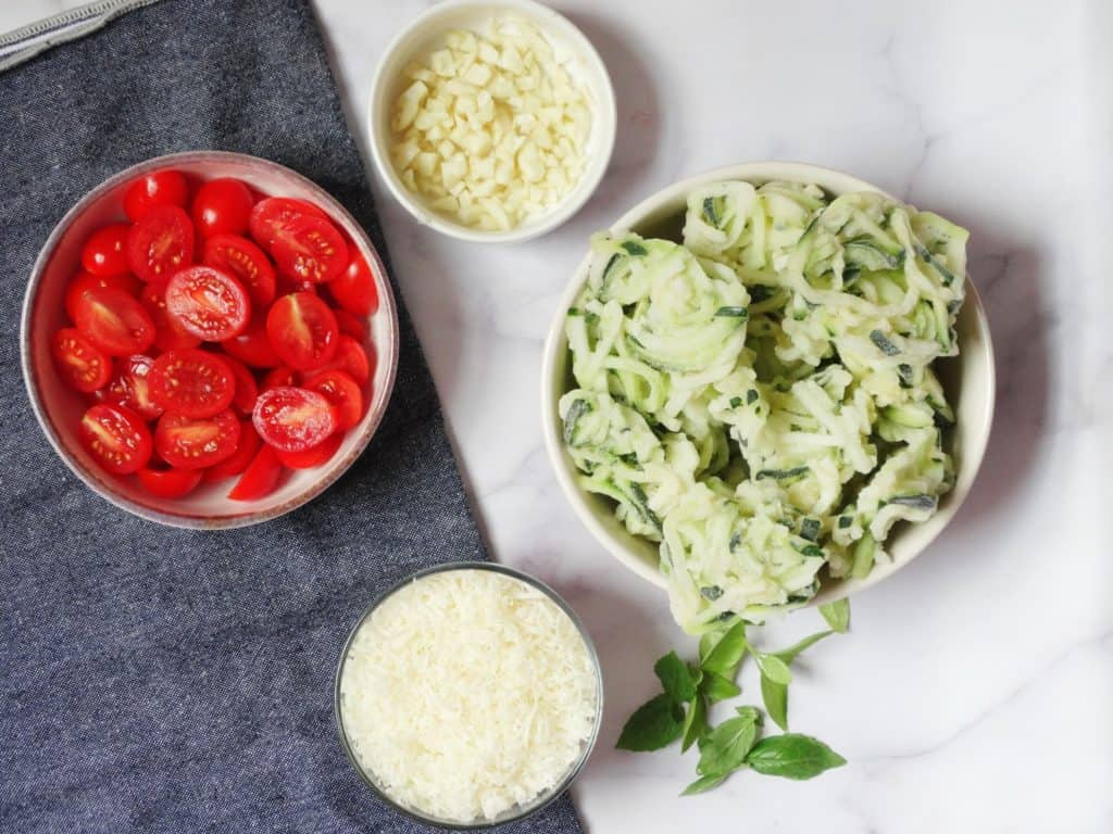 zucchini noodles recipe ingredients: tomatoes, cheese, garlic, and zoodles