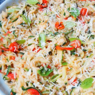 garlic parmesan zucchini noodles with tomatoes on a plate and white background