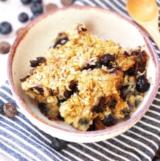 blueberry baked oatmeal in a small dish surrounded by fresh blueberries and chocolate