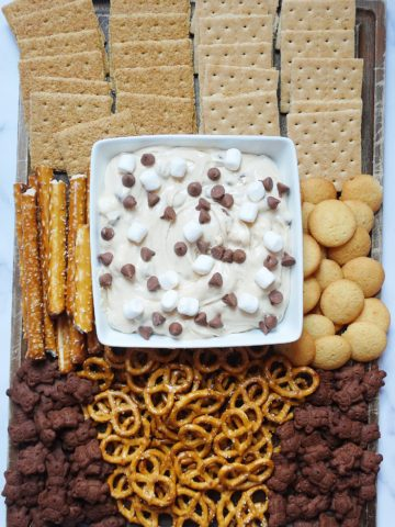 smores snack board with pretzels, graham crackers, wafers, and teddy grahams