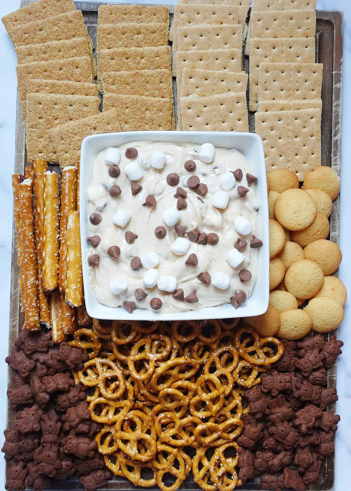 kid-friendly smores snack board with pretzels, graham crackers, wafers, and teddy grahams