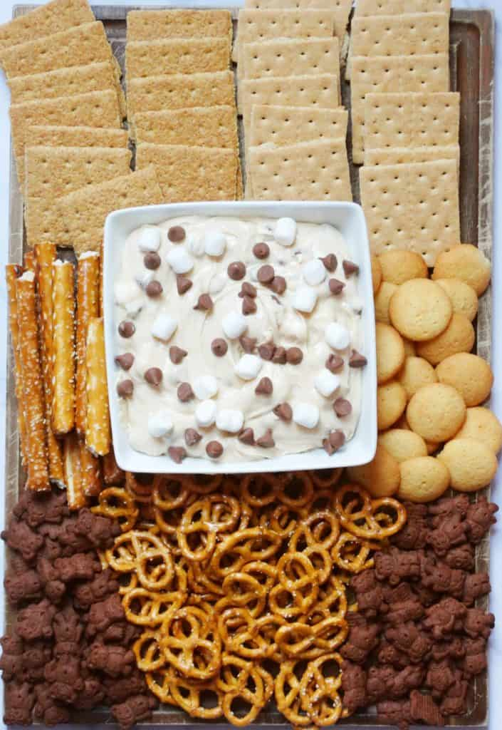 smores dip snack board with pretzels, graham crackers and wafers