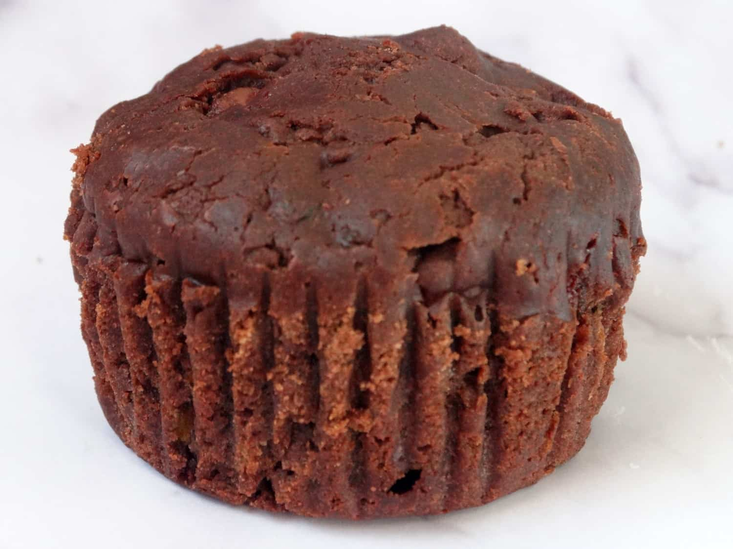 close up of a chocolate zucchini muffin on a white background