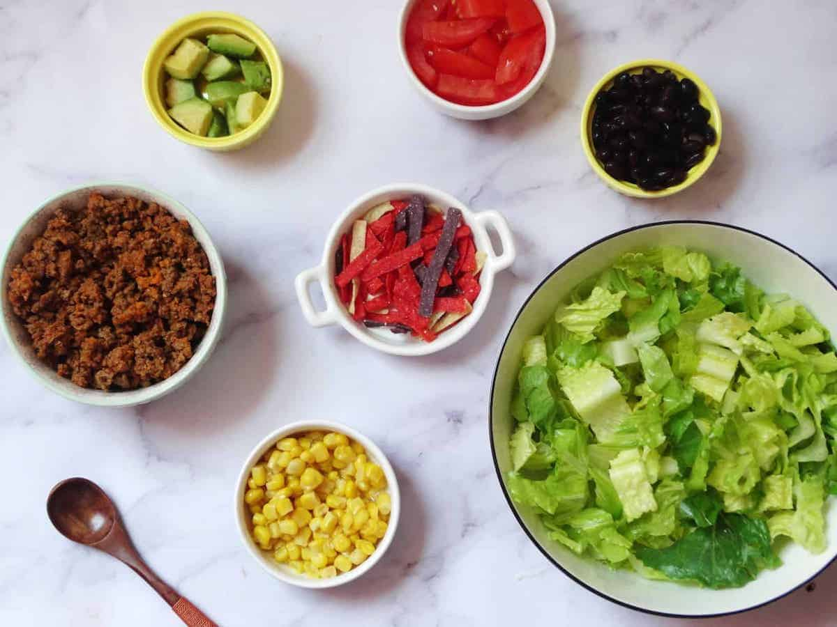 lettuce, corn, avocado, beans, beef, and tomatoes separated in bowls